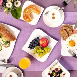 Gedeckter Frühstückstisch mit Obst, Kaffee, Gebäck